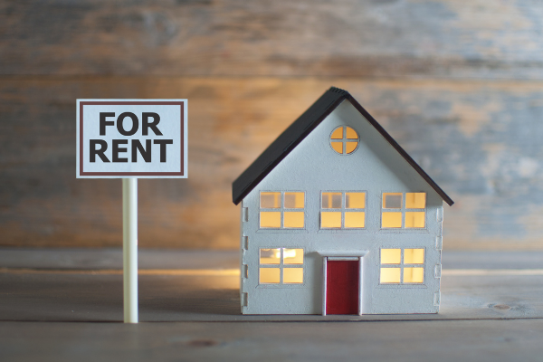 Figurine home next to a 'For Rent' sign with a wooden background.